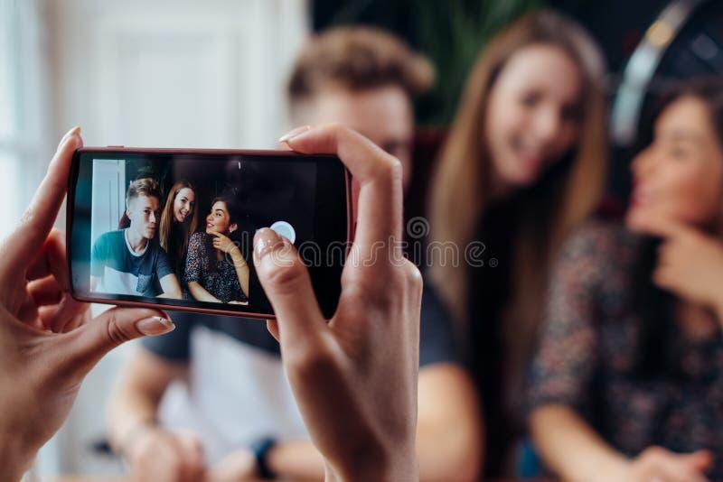 Mani femminili che prendono foto con lo smartphone di giovani amici allegri, fondo vago fotografia stock