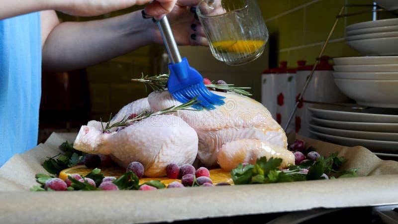 Mani femminili che spazzolano intero pollo crudo con la salsa di torrefazione nella torrefazione Pan With Oranges Cranberries e d fotografie stock