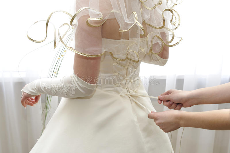 Mani femminili che stringono un corsetto alla sposa immagine stock