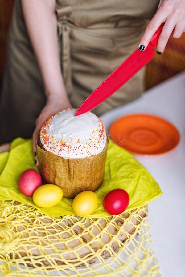 Mani femminili che tagliano il dolce di Pasqua Fuoco selettivo immagine stock