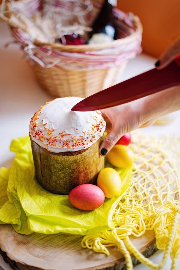Mani femminili che tagliano il dolce di Pasqua Fuoco selettivo immagine stock libera da diritti
