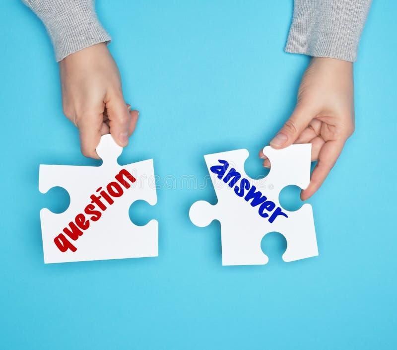 mani femminili che tengono i puzzle bianchi della grande carta con un'iscrizione di domande e risposte fotografie stock