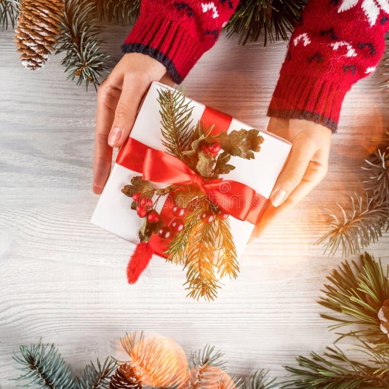 Mani femminili che tengono il contenitore di regalo di Natale su fondo di legno bianco con i rami dell'abete, pigne Tema del buon fotografia stock libera da diritti