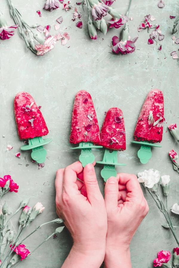 Mani femminili che tengono il ghiaccio del ghiacciolo di frutti Gelato rosso casalingo sul fondo verde chiaro del tavolo da cucin immagine stock libera da diritti