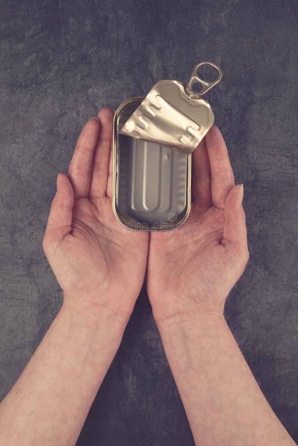 Mani femminili che tengono il pesce vuoto aperto Tin Can della sardina fotografie stock