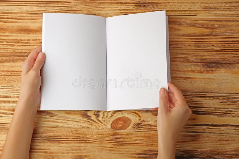Mani femminili che tengono l'opuscolo aperto dello spazio in bianco fotografia stock