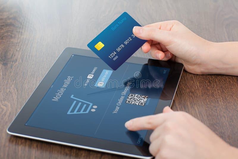 Mani femminili che tengono la carta di credito e una compressa nell'ufficio e fotografia stock