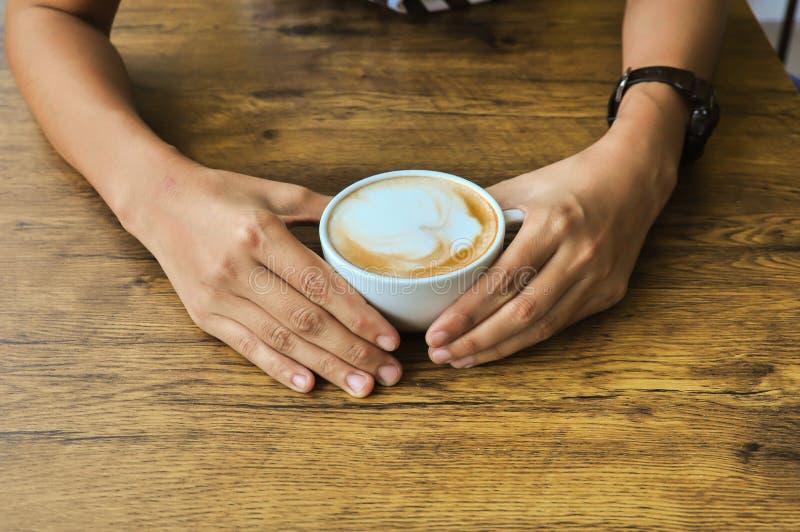 Mani femminili che tengono le tazze di caffè sul backg di legno rustico della tavola fotografie stock