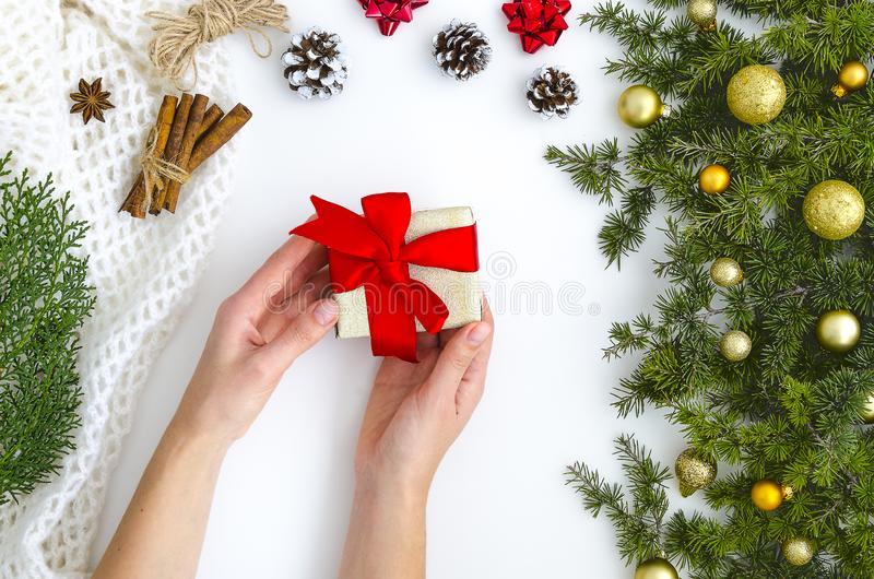 Mani femminili che tengono presente con l'arco rosso su fondo scintillante bianco con l'albero di abete, palle dorate Contesto fe fotografia stock libera da diritti