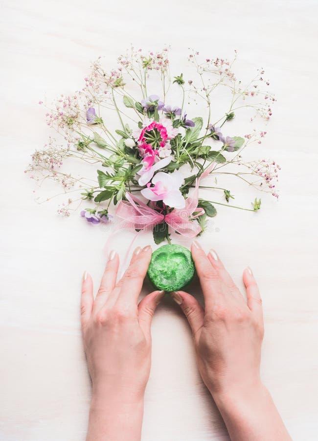 Mani femminili che tengono sapone verde fatto a mano naturale con le erbe ed i fiori fragranti, saponeria organica, vista superio fotografia stock