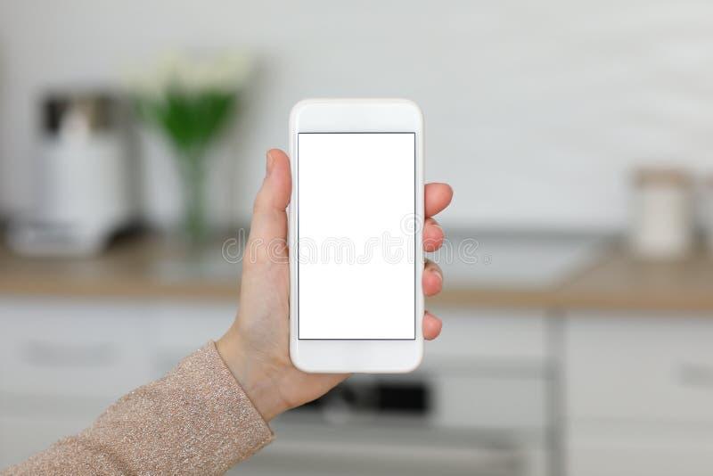 Mani femminili che tengono telefono bianco con lo schermo isolato nella sala immagine stock