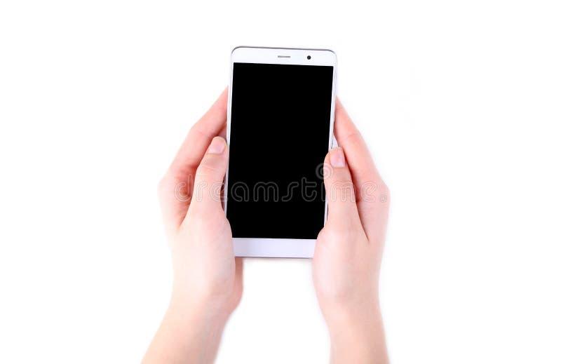 Mani femminili che tengono telefono cellulare con lo schermo in bianco isolato su bianco fotografia stock