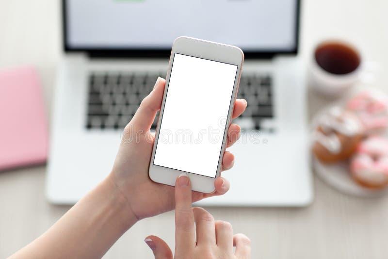 Mani femminili che tengono telefono con lo schermo ed il computer portatile fotografia stock libera da diritti