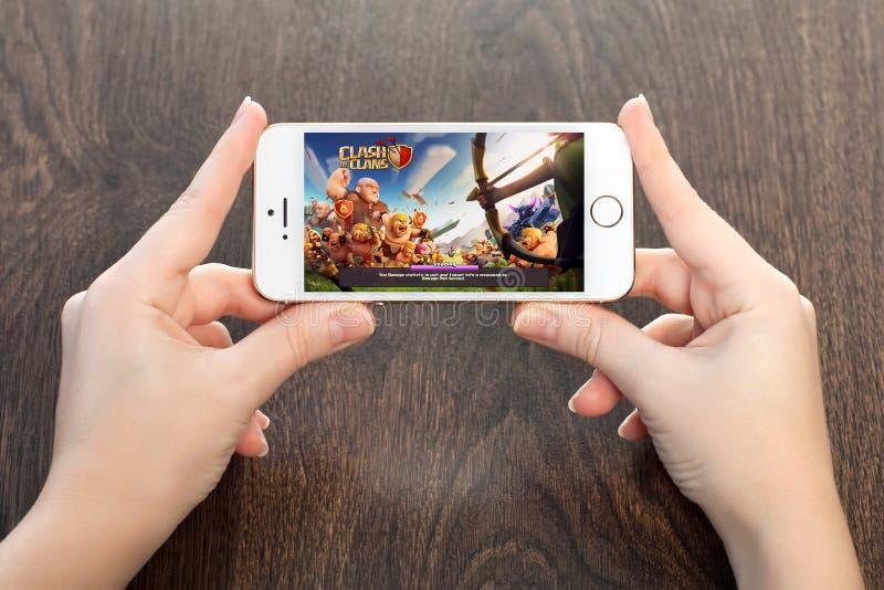 Mani femminili che tengono un iPhone bianco con lo scontro dei clan sulla s fotografia stock libera da diritti