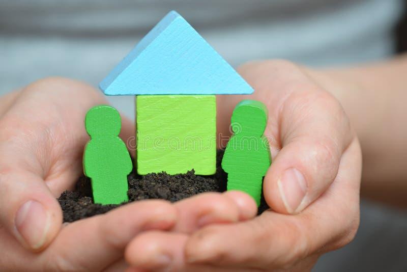 Mani femminili che tengono un pezzo di terra con la casa di legno Concetto ecologico della casa, della famiglia, della costruzion fotografie stock libere da diritti