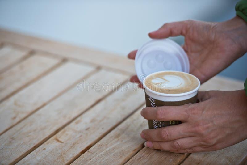 Mani femminili che tengono una tazza di caffè di carta immagini stock