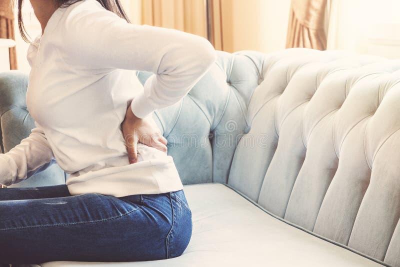 Mani femminili che toccano dolore alla schiena che si siede in sofà che riposa a casa massaggio ferito della vita bassa della gio fotografia stock libera da diritti