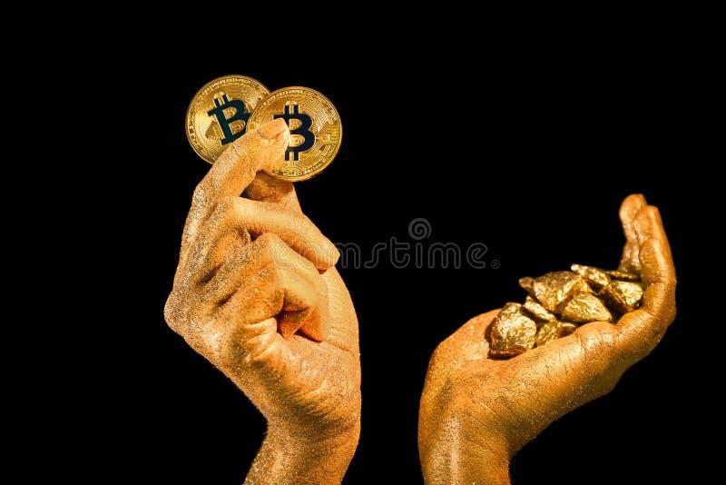 Mani femminili con i bitcoins e pepite di oro su fondo nero fotografia stock