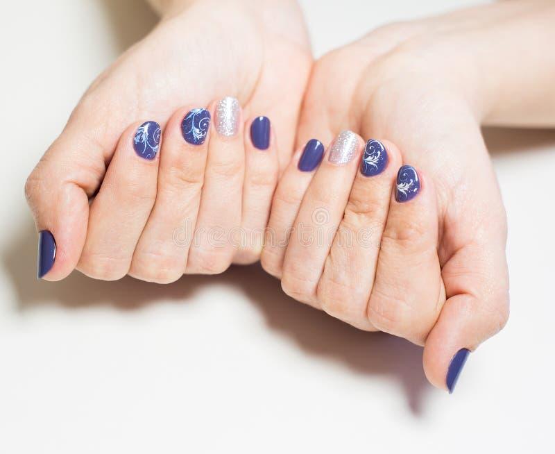 Mani femminili con il manicure blu e d'argento professionale immagini stock