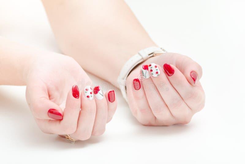 Mani femminili con il manicure, smalto rosso Priorità bassa bianca immagine stock