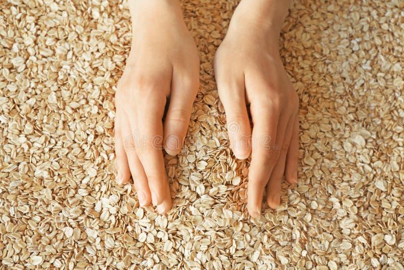 Mani femminili con il mucchio della farina d'avena cruda fotografie stock