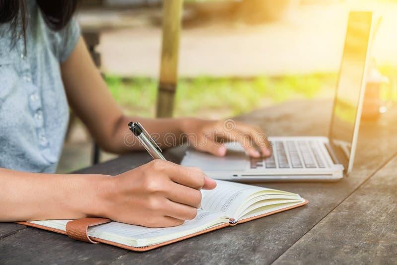Mani femminili con il taccuino di scrittura della penna immagini stock libere da diritti