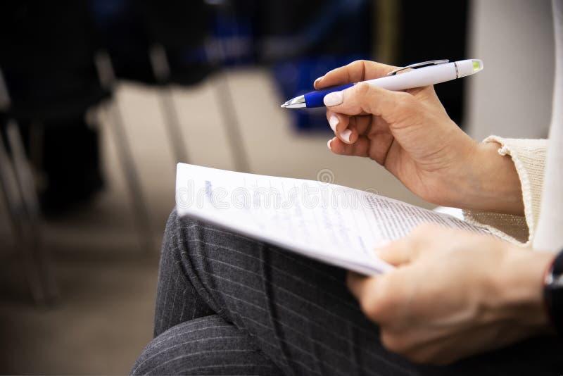 Mani femminili con pezzo di carta e una penna a sfera immagini stock libere da diritti