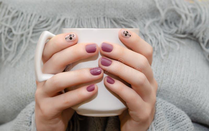Mani femminili con progettazione rosa scura del chiodo fotografia stock libera da diritti