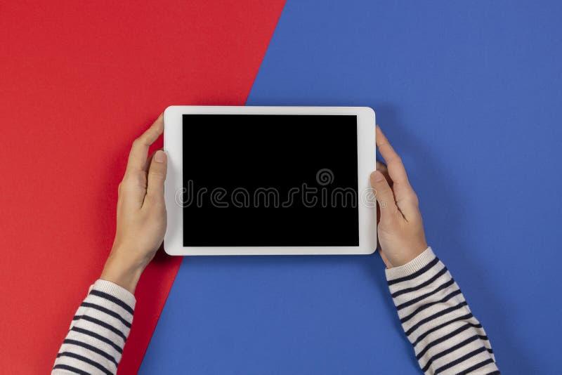 Mani femminili con tablet computer su sfondo blu e rosso Vista dall'alto immagini stock libere da diritti