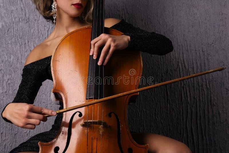 Mani femminili con un arco sulle corde del violoncello immagine stock libera da diritti