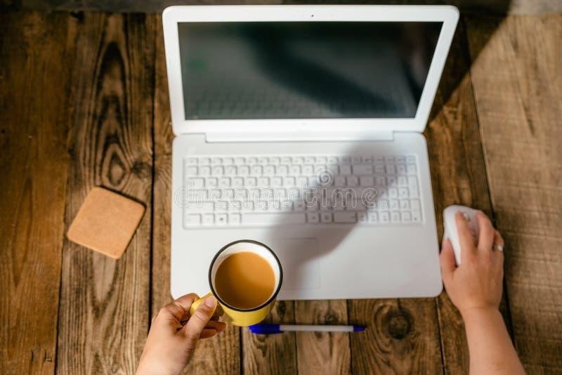 Mani femminili con un taccuino e una tazza di caffè bianchi fotografia stock