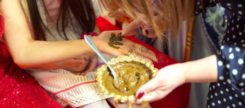 Mani femminili decorativo colorate da hennè con la tazza Tenga un arco fotografia stock libera da diritti