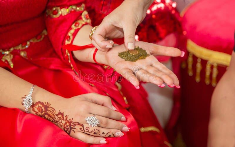 Mani femminili decorativo colorate da hennè con la tazza Tenga una ciotola con la noce di cocco nell'ambito delle sue mani Hennè  fotografia stock libera da diritti