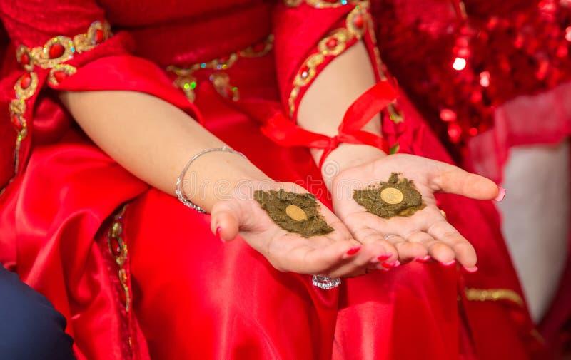 Mani femminili decorativo colorate da hennè con la tazza Tenga una ciotola con la noce di cocco nell'ambito delle sue mani Hennè  fotografia stock