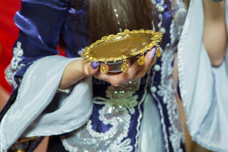 Mani femminili decorativo colorate da hennè con la tazza Tenga una ciotola con la noce di cocco nell'ambito delle sue mani Misto  fotografia stock libera da diritti