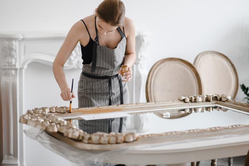 Mani femminili dell'artigiano che lavorano ad una grande cornice di legno fotografia stock libera da diritti