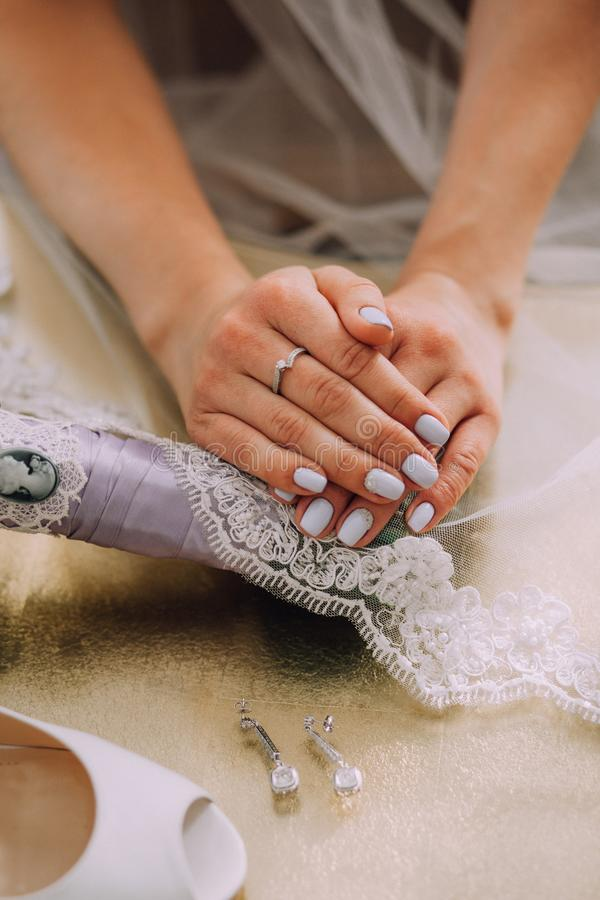 Mani femminili della sposa con un bello manicure blu, anello sul dito Velo di menzogne con pizzo accanto agli orecchini e fotografia stock libera da diritti