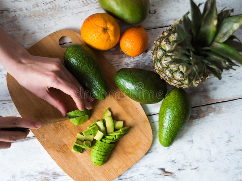 Mani femminili di vista superiore che cucinano con l'avocado alla tavola in cucina domestica immagine stock libera da diritti