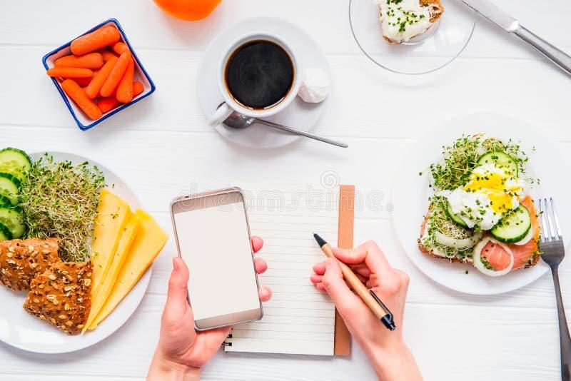 Mani femminili di vista superiore che tengono Smart Phone e che scrivono in taccuino sulla tavola di legno bianca servita con i p immagini stock libere da diritti