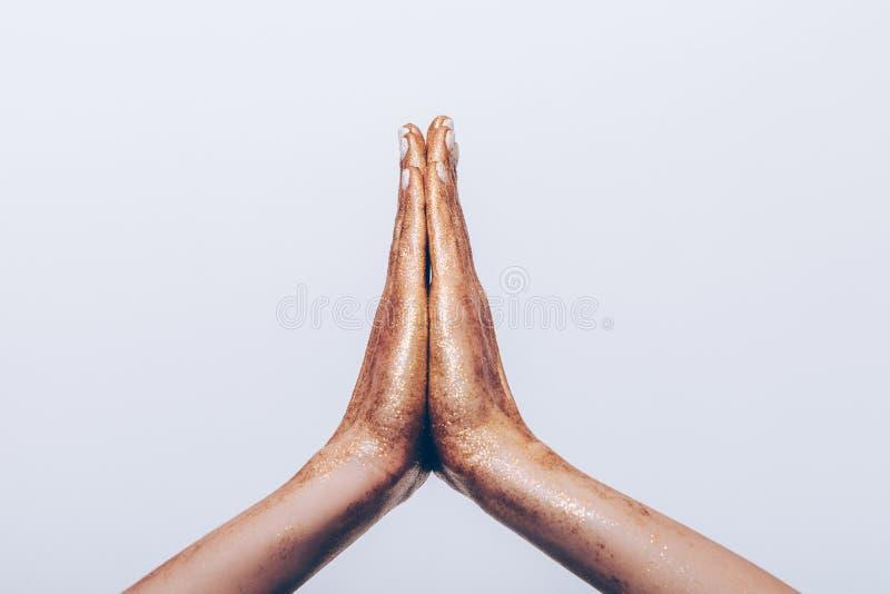 Mani femminili dorate nel gesto di preghiera fotografia stock libera da diritti