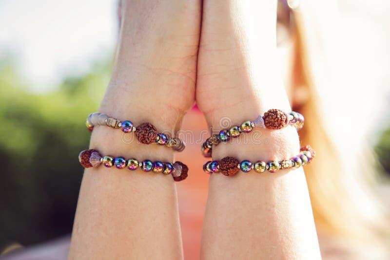 Mani femminili in mudra del namaste con i braccialetti fotografia stock