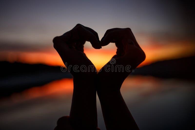 Mani femminili sotto forma di cuore sul cielo crepuscolare ed arancio Vista orizzontale immagini stock libere da diritti