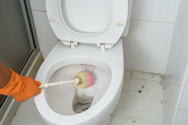Mani in guanti arancio che puliscono WC, toilette, lavabo facendo uso della spazzola fotografia stock