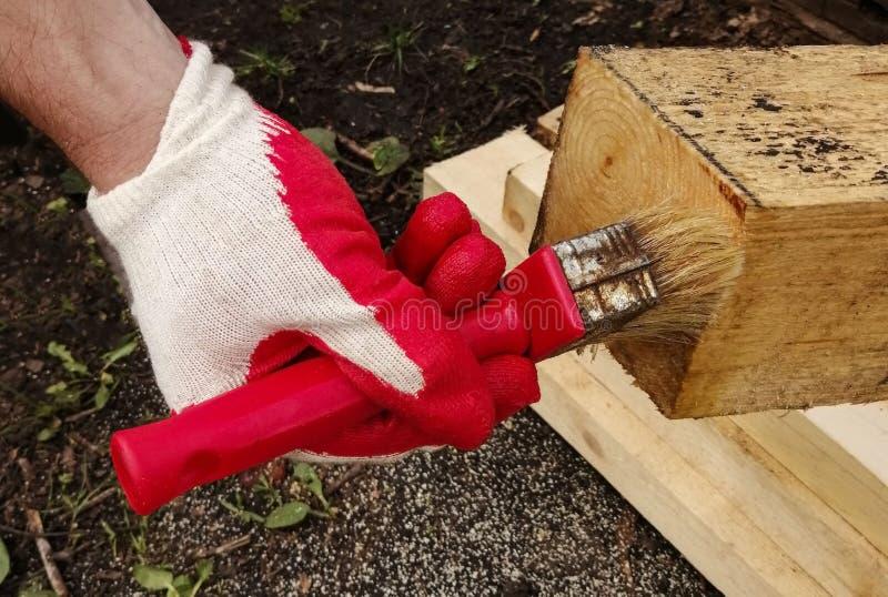 Mani in guanti con una spazzola fotografie stock