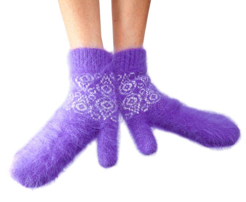 Mani in guanti lilla lanuginosi su un fondo bianco fotografie stock