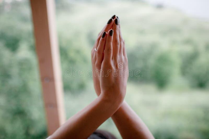 Mani intreccianti mani femminili sul fondo della natura immagine stock