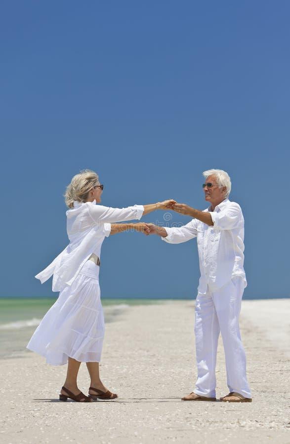Mani maggiori felici della holding delle coppie su una spiaggia fotografie stock