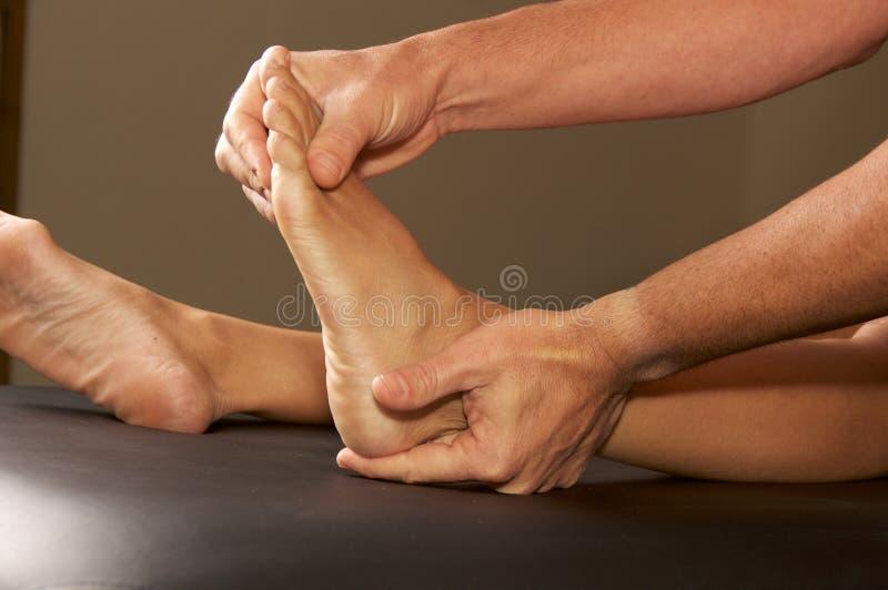 Mani maschii che flettono piede femminile immagini stock libere da diritti