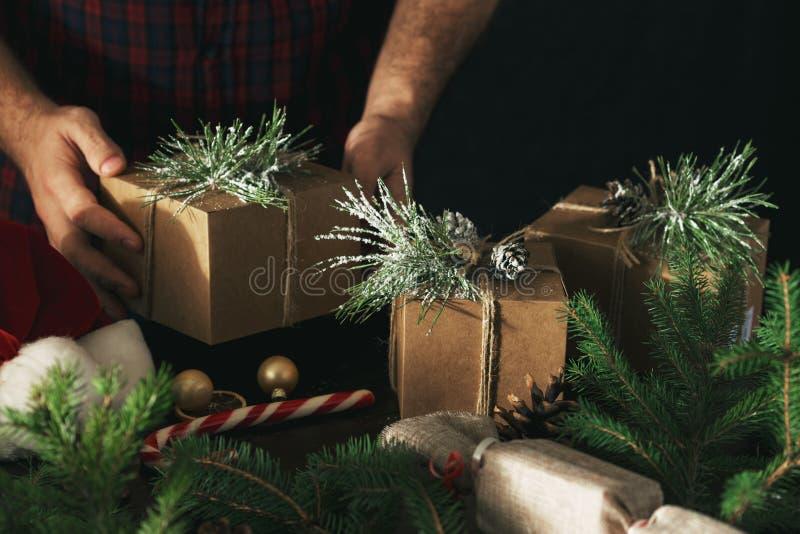 Mani maschii che tengono il fondo di Natale dei contenitori di regalo di Natale Spostamento dei presente fotografia stock libera da diritti