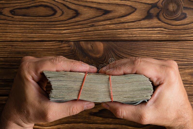 Mani maschii che tengono un batuffolo spesso di soldi immagine stock